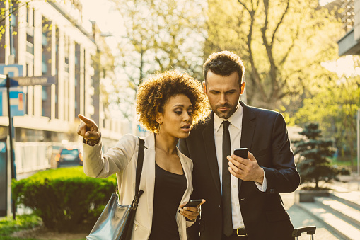 Outdoor Portrait Of Two Business People With Smart Phones Stock Photo - Download Image Now