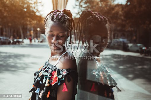 istock Outdoor portrait of young African-American woman near a glass wall 1047001660