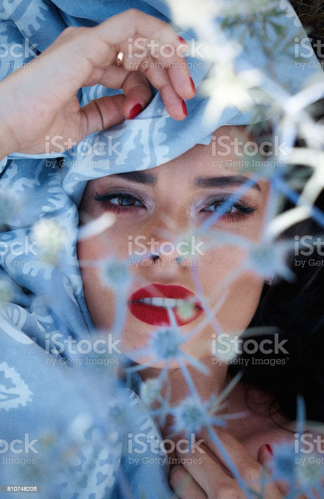 Outdoor portrait of young beautiful oriental woman with blue scarf around head stock photo