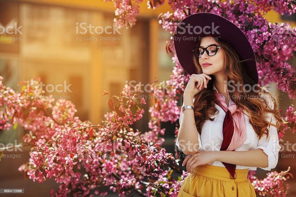 Outdoor portrait of young beautiful fashionable lady posing near flowering – Foto