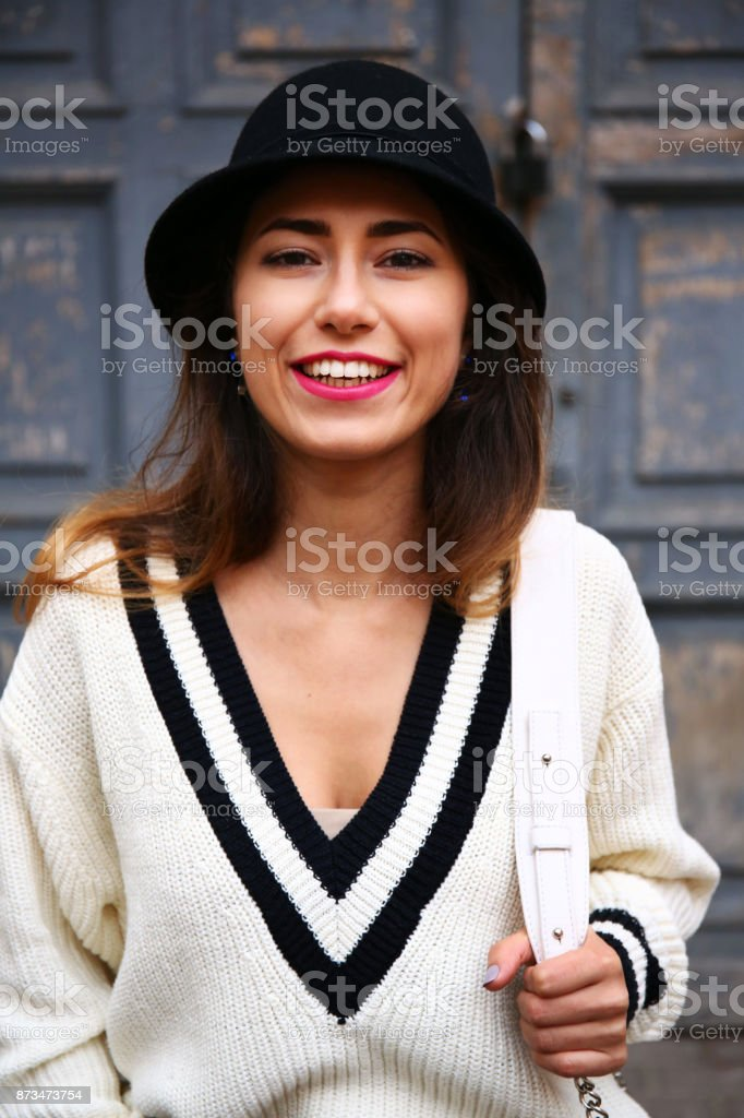 Outdoor portrait of young beautiful happy smiling girl posing on street. Model looking at camera. Lady wearing stylish winter clothes. Female fashion. stock photo