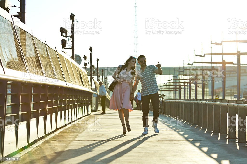 Outdoor portrait of young couple in the city at sunset Full lenght portrait of contemporary happy young couple holding their hands and walking in the city at sunset. 2015 Stock Photo