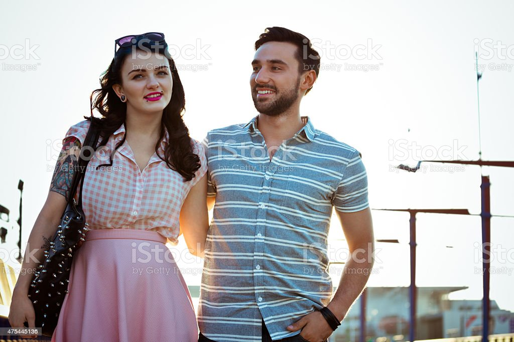 Outdoor portrait of young couple in the city at sunset Portrait of contemporary happy young couple embracing and walking in the city at sunset. Woman has tattoo on her arm. 2015 Stock Photo