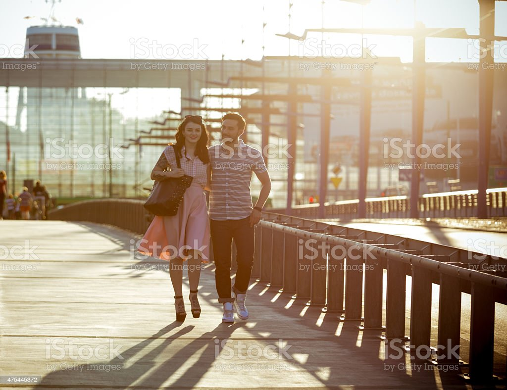 Outdoor portrait of young couple in the city at sunset Full lenght portrait of contemporary happy young couple embracing and walking in the city at sunset. 2015 Stock Photo