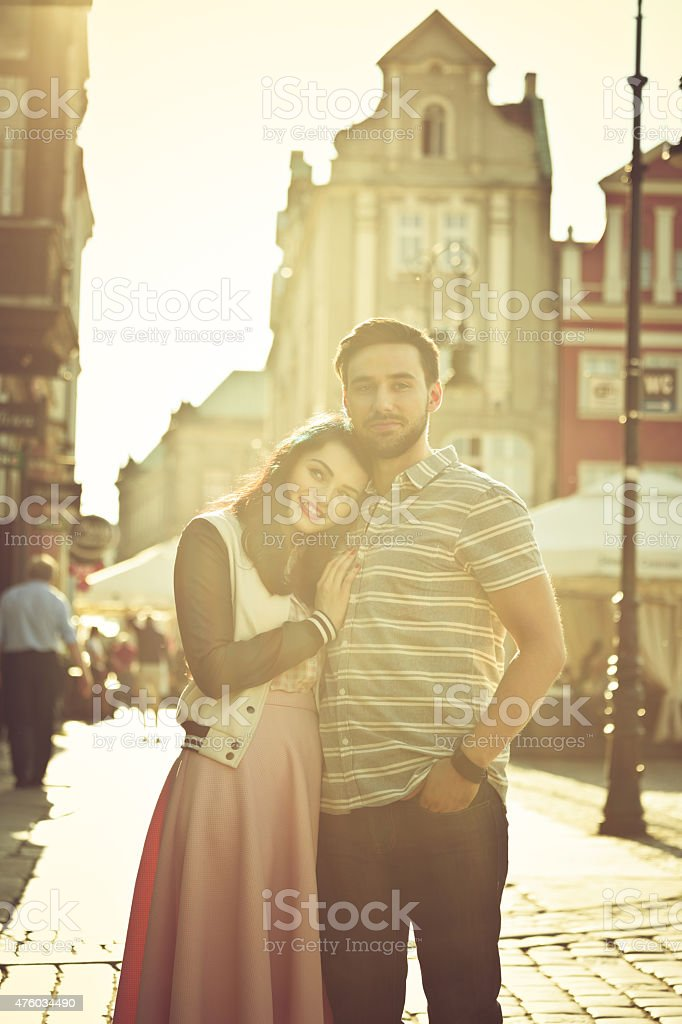 Outdoor portrait of young couple in the city at sunset Portrait of contemporary young couple in the city at sunset, embracing and smiling at camera. 2015 Stock Photo
