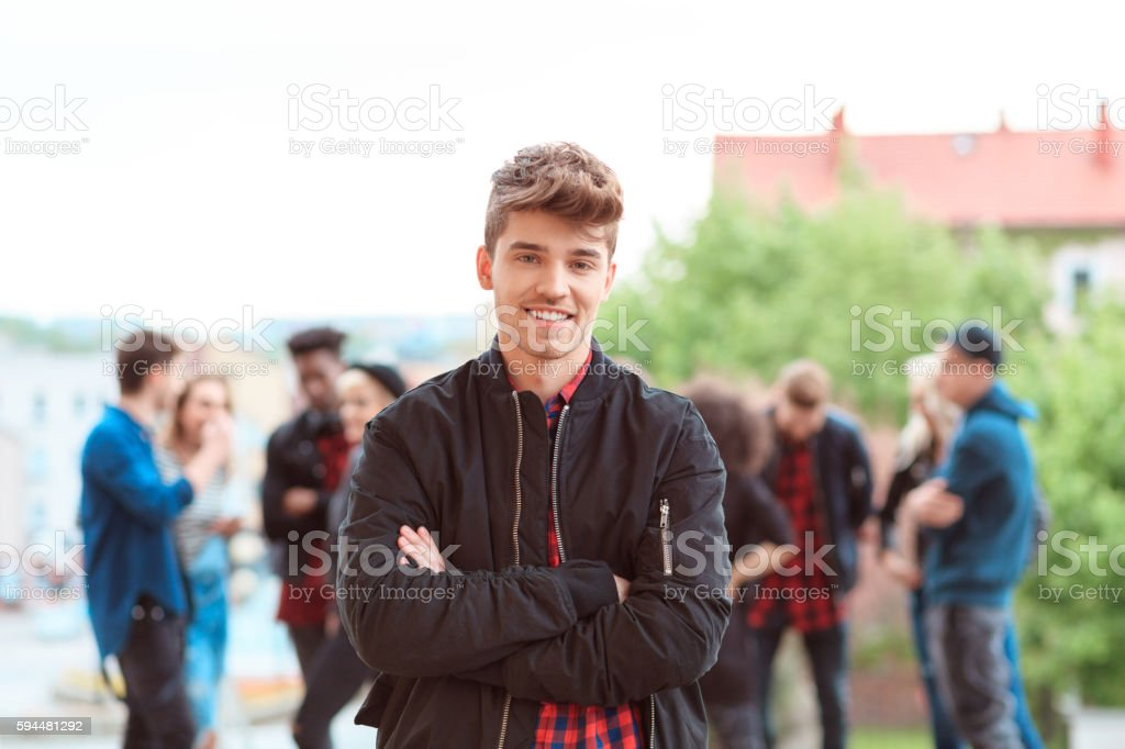 Outdoor portrait of young guy smiling Outdoor portrait of young guy smiling at camera. Multi ethnic group of people in the background. 20-29 Years Stock Photo