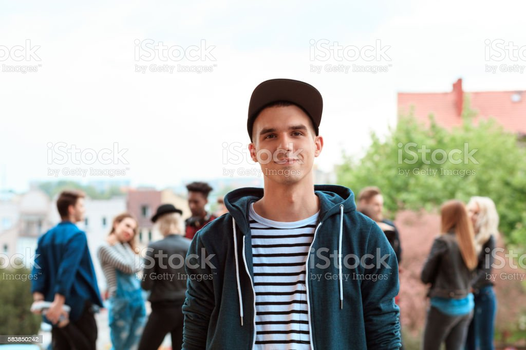 Outdoor portrait of young man Outdoor portrait of young man smiling at camera. Multi ethnic group of people int he background. 20-29 Years Stock Photo