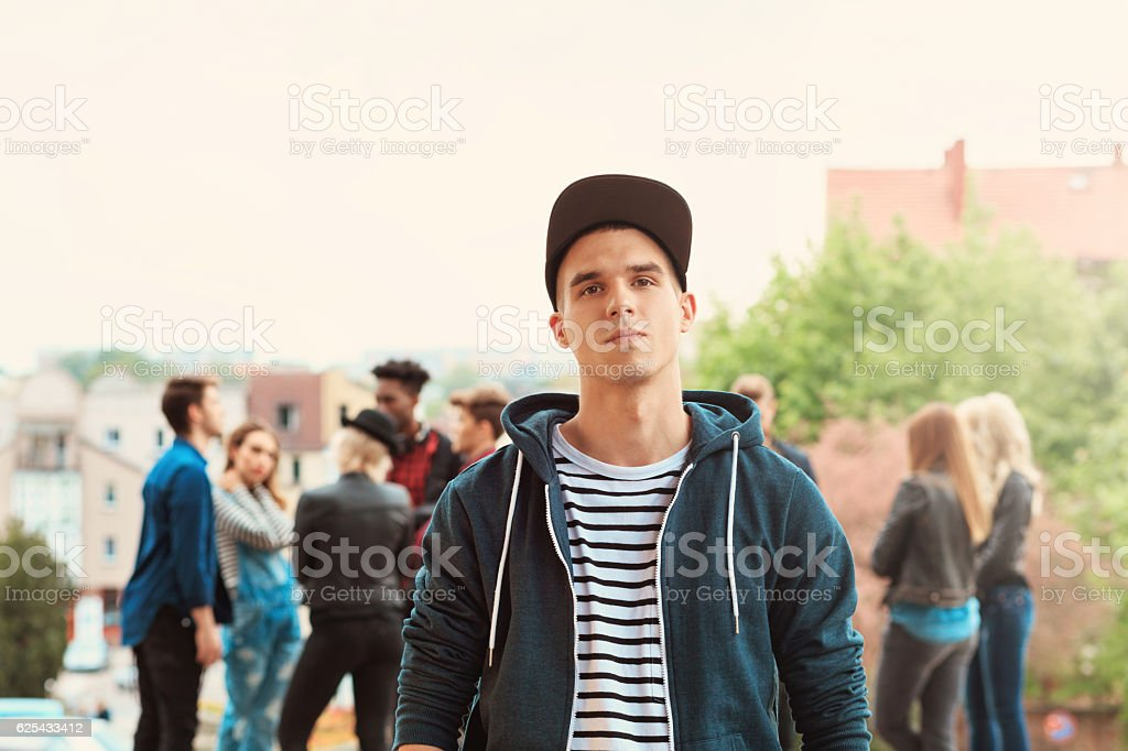 Outdoor portrait of young man Outdoor portrait of young man looking at camera. Multi ethnic group of people int he background. 20-29 Years Stock Photo