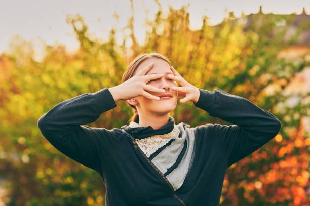 金色の光の中で若い十代の少女の屋外肖像画、手で顔を隠す - gen z ストックフォトと画像