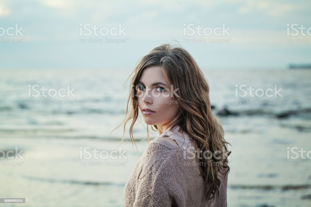 Outdoor Portrait of Young Woman Looking at Camera on Natural Background with Copy Space stock photo