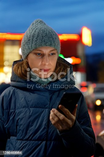 Outdoor portrait of young woman using her smartphone on night city. Shallow focus.
