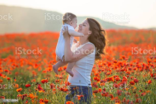 Outdoor portrait. Young mother and her daughter enjoy life time together on a poppy field . Concept of love and happy family. Poppy meadow