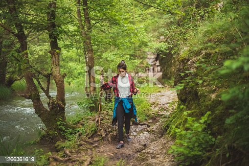 A young woman is walking down the path in dense woods. She's passing by the stream at the moment. She's using a walking stick she found on the way to help her move around.