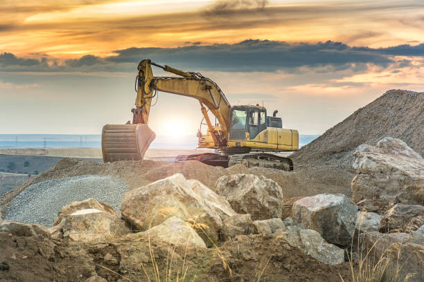 Outdoor quarry with heavy machinery Outdoor quarry with heavy machinery or road construction construction machinery stock pictures, royalty-free photos & images