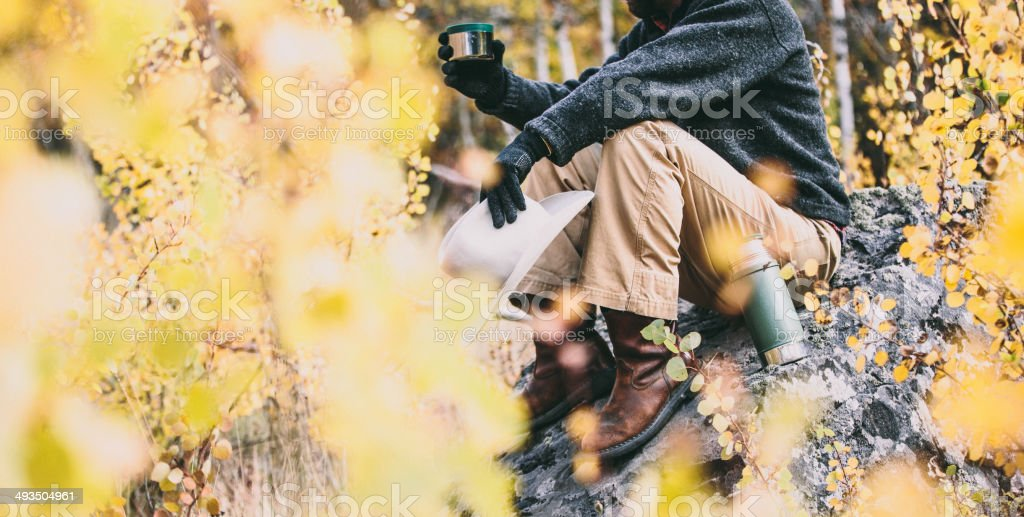 Outdoor ranch worker takes break with coffee on rock stock photo