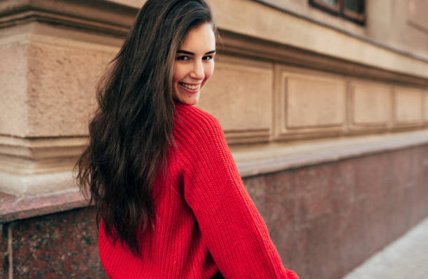 Outdoor rear view portrait of beautiful young brunette woman smiling, follow me on the city street. Pretty female model in trendy knitted red sweater walking in the town. Travel, people, lifestyle stock photo