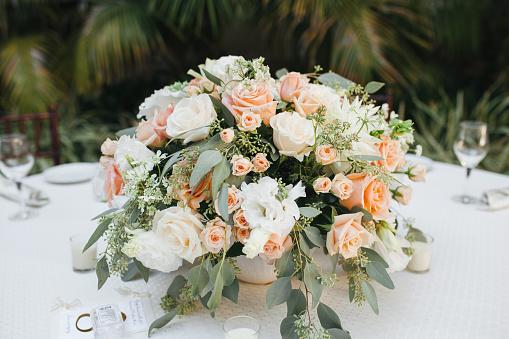 Outdoor reception table decor - round tables with white tablecloths and floral center pieces