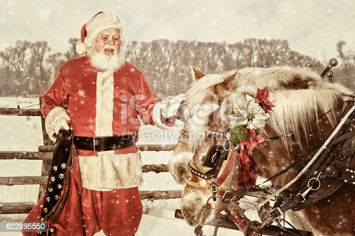Santa in an outdoor setting talking to his team of horses.  He is holding a set of handbells in his right hand.  A light winter snow is falling.