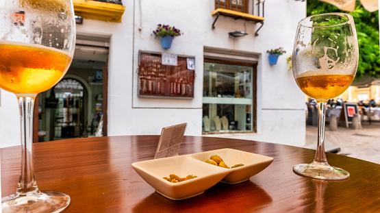 Outdoor scene having a few beers and olives at the table of a bar in an area with a lot of tourism, Córdoba Andalucía