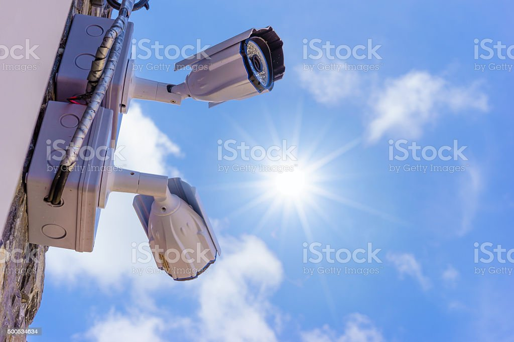 outdoor security cctv cameras against blue sky and sunshine. stock photo