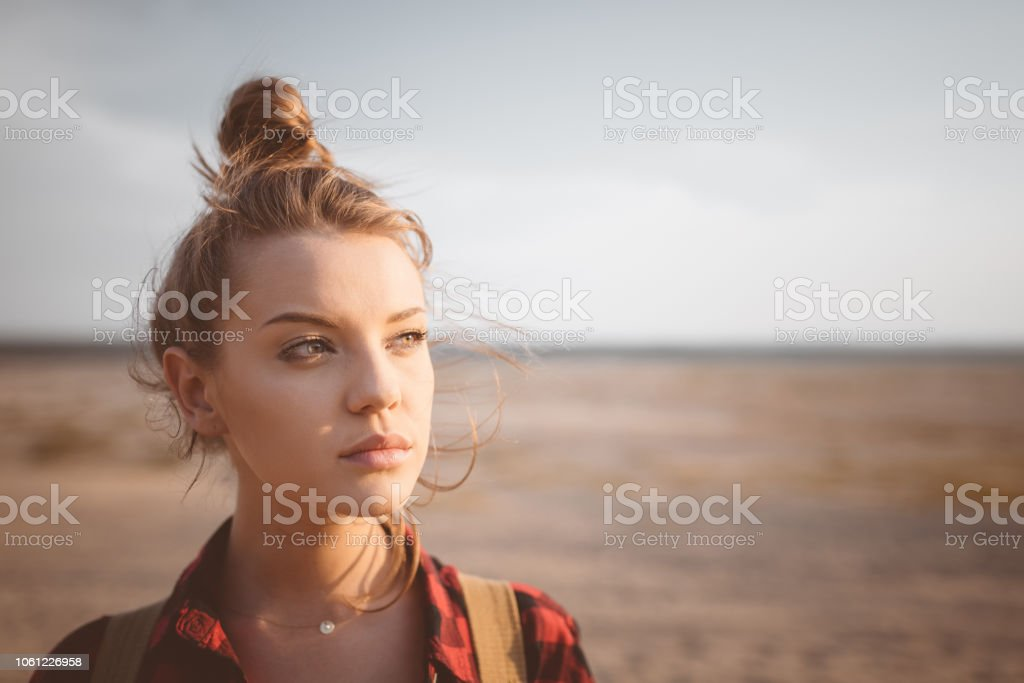 Outdoor shot lonely young woman on desert Outdoor shot of beautiful pensive young women standing against desert. Close up of face. Adolescence Stock Photo