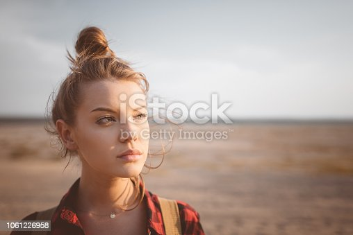 Outdoor shot of beautiful pensive young women standing against desert. Close up of face.