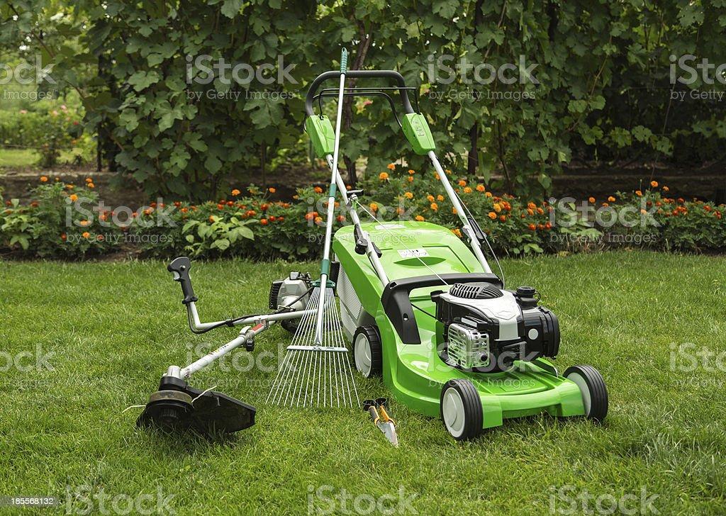 Outdoor shot of garden equipment Green lawnmower, weed trimmer, rake and secateurs in the garden Black Color Stock Photo