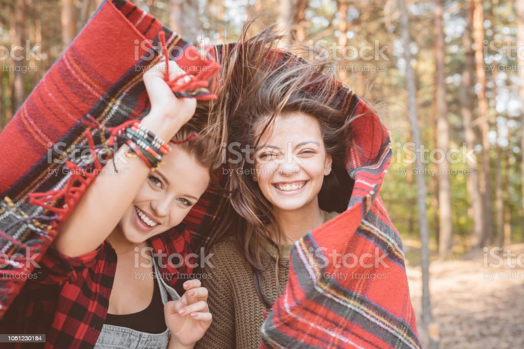 Outdoor shot of happy friends Outdoor shot of two excited young women covering by checkered blanket, laughing at camera. Close up of faces. Adolescence Stock Photo