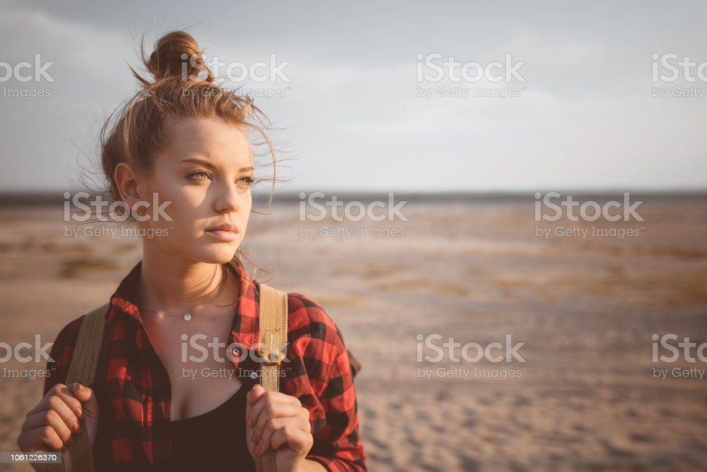 Outdoor shot of lonely young woman on the desert Outdoor shot of beautiful pensive young woman standing against desert, looking away. Close up of face. Adolescence Stock Photo