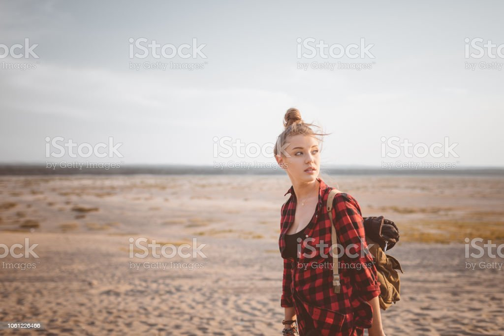 Outdoor shot of lonely young woman on the desert Outdoor shot of beautiful pensive young woman standing against desert, looking away, holding backpack. Adolescence Stock Photo