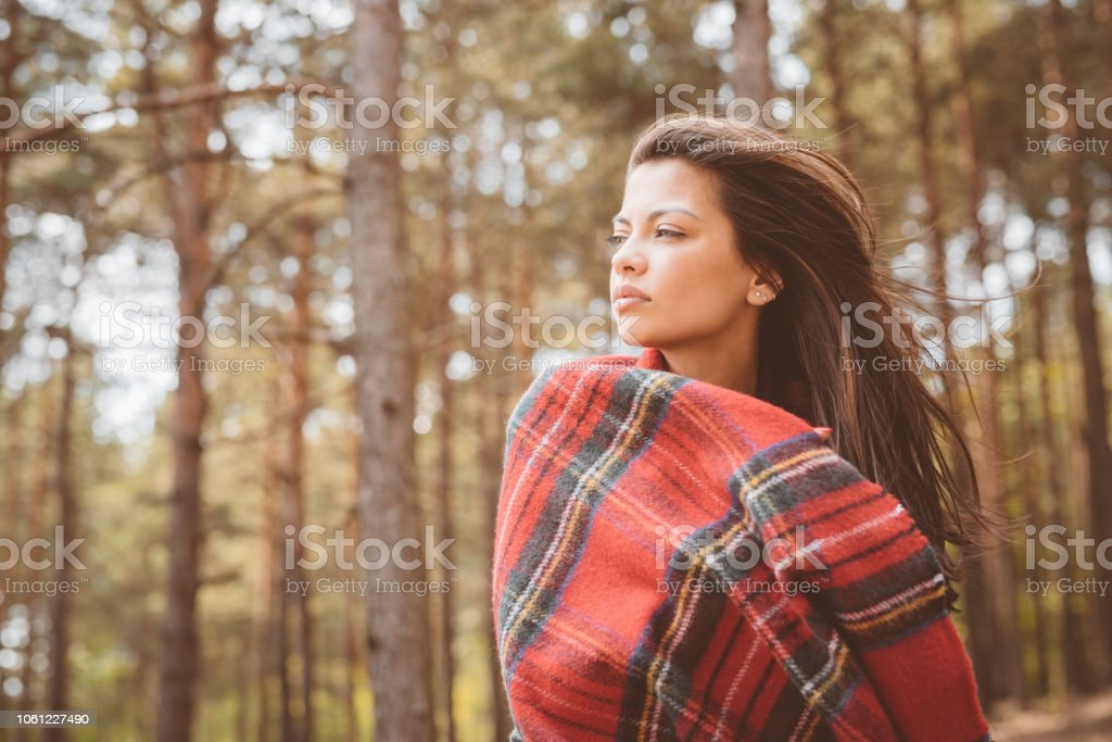 Outdoor shot of lonely young woman Outdoor shot of beautiful pensive young woman standing in the forest and covering by checkered blanket, looking away. Close up of face. Adolescence Stock Photo