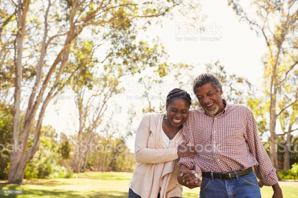 Outdoor Shot Of Mature Couple Walking In Park Together stock photo