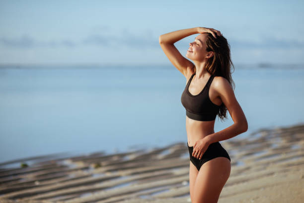 Outdoor shot of smiling young female model in bikini standing against blue sky. stock photo
