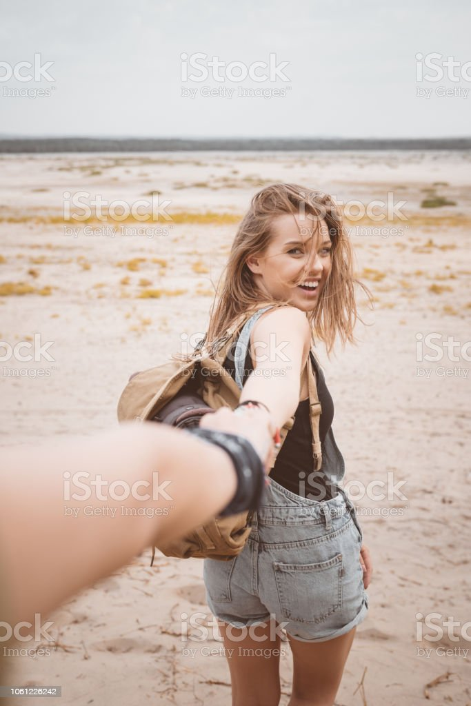 Outdoor shot of smiling young woman on the desert Outdoor shot of beautiful young woman standing against desert, holding hand with friend and smiling at the camera. Adolescence Stock Photo