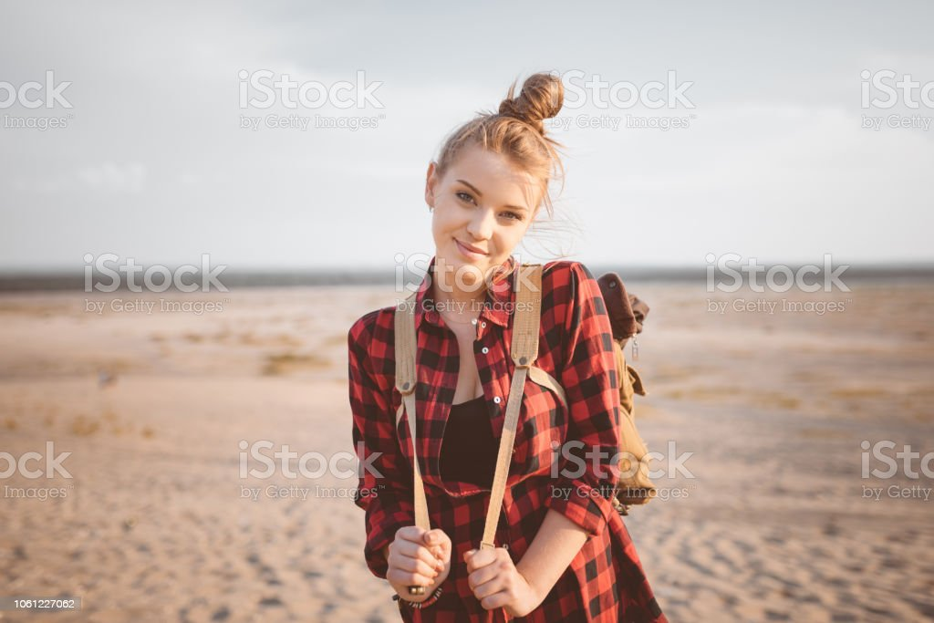Outdoor shot of smiling young woman on the desert Outdoor shot of beautiful young woman standing against desert, holding backpack and smiling at the camera. Adolescence Stock Photo