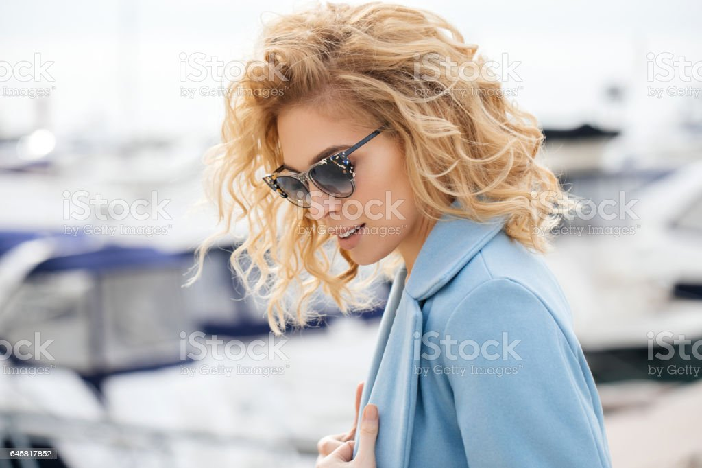 Outdoor shot of young beautiful woman on a pier stock photo