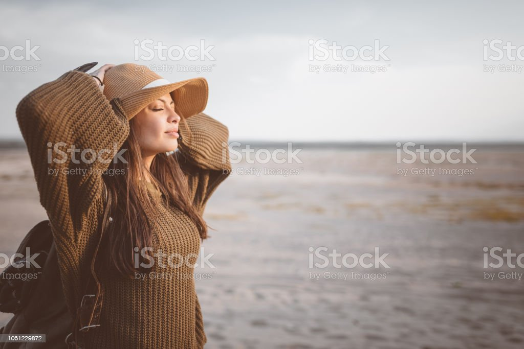Outdoor shot of young woman resting on the desert Outdoor shot of beautiful young woman standing against desert, holding backpack and enjoying sunset. Adolescence Stock Photo