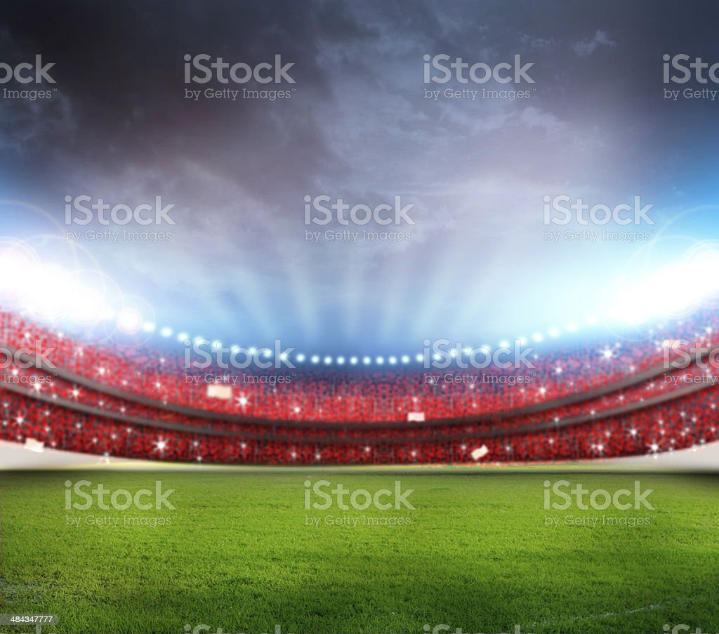 Outdoor stadium with overcast sky and green grass stock photo