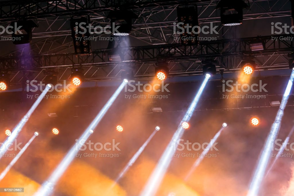 outdoor stage during performance with yellow spotlights and blue...