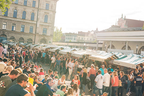 Outdoor street food festival in Ljubljana Ljubljana, Slovenia - July 15, 2016: People enjoing outdoor street food festival - Open Kitchen - sitting on stairs under the sun, eating and drinking variety of dishes cooked at the food stalls.  food festival stock pictures, royalty-free photos & images