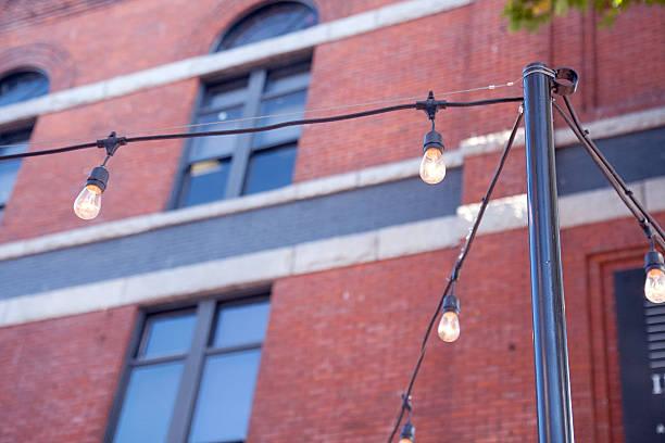 outdoor grüne lichter von einem backstein-gebäude - terrassen lichterketten stock-fotos und bilder
