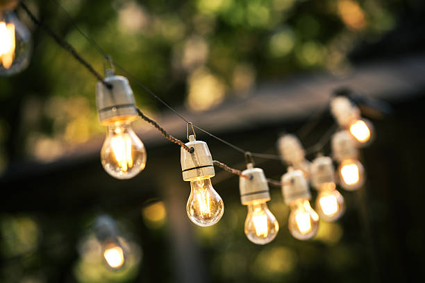 outdoor string lights hanging on a line in backyard - lampenlicht stock-fotos und bilder