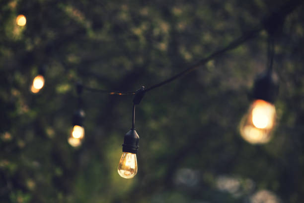 outdoor string lights hanging on a line in backyard stock photo