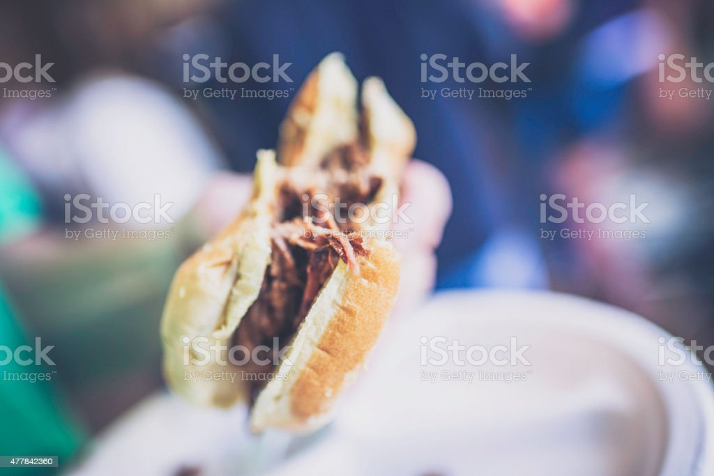 Outdoor summer party. Man eating BBQ sandwich. stock photo