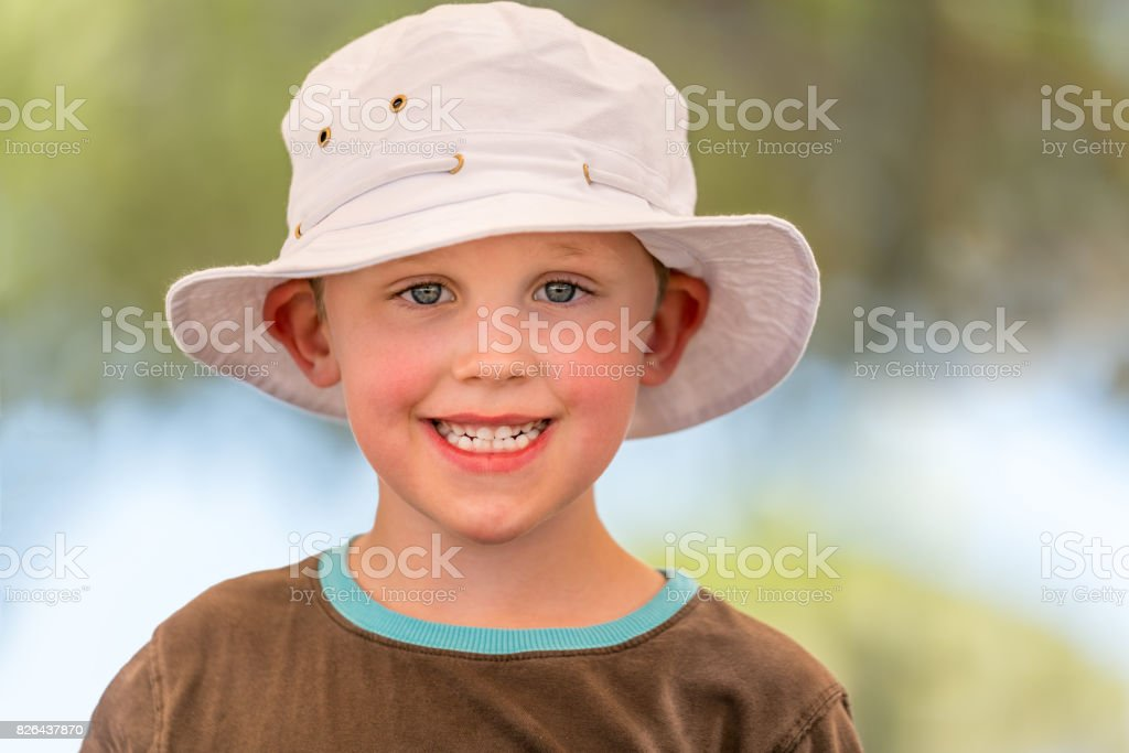 Outdoor summer portrait of cute smiling boy in white hat. royalty-free stock photo