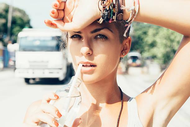 Outdoor summer portrait of woman drinks water stock photo