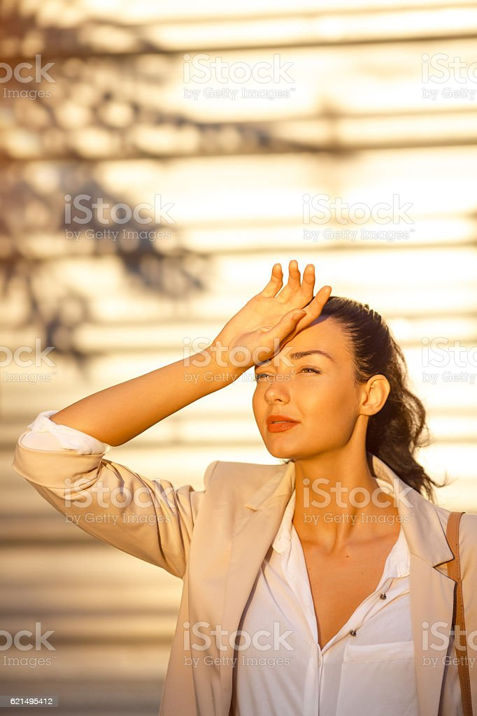 Outdoor summer portrait of young girl in suit suffering sun stock photo