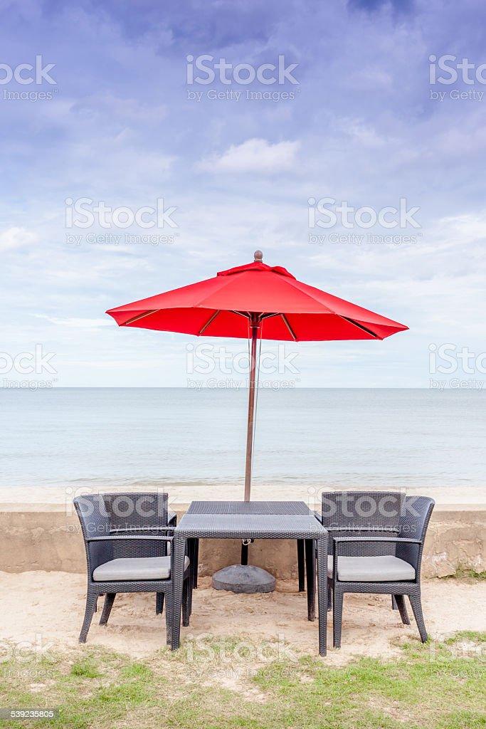 Juego de mesas al aire libre, playa, sillas y sombrilla con hermosas rojo foto de stock libre de derechos