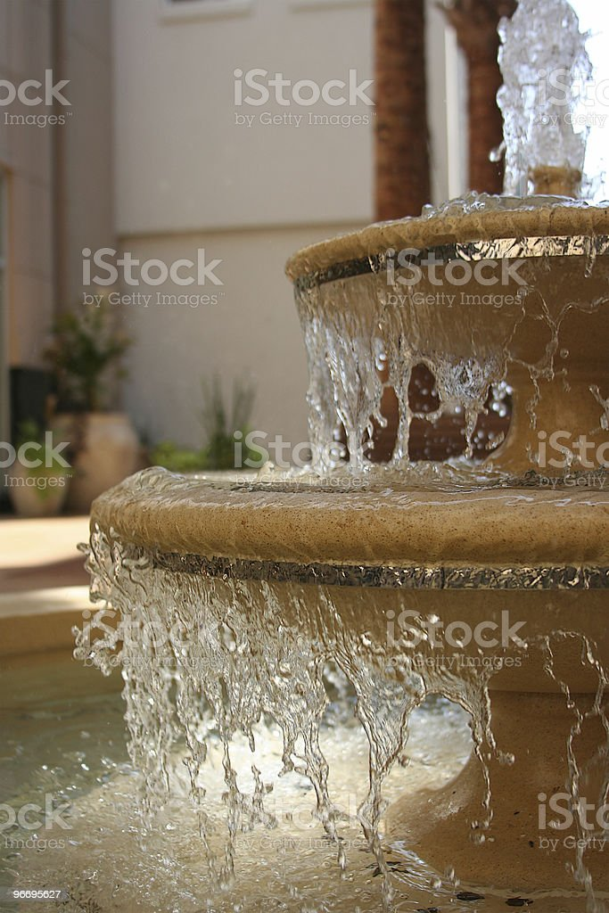 Outdoor Tiered Patio Fountain Peacefully Cascading Water Into A Pool stock photo