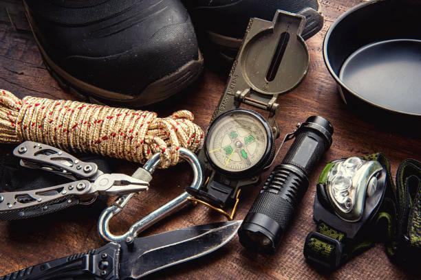 outdoor-reiseausrüstung planung für einen berg-trekking-camping-trip auf holzhintergrund - überleben stock-fotos und bilder